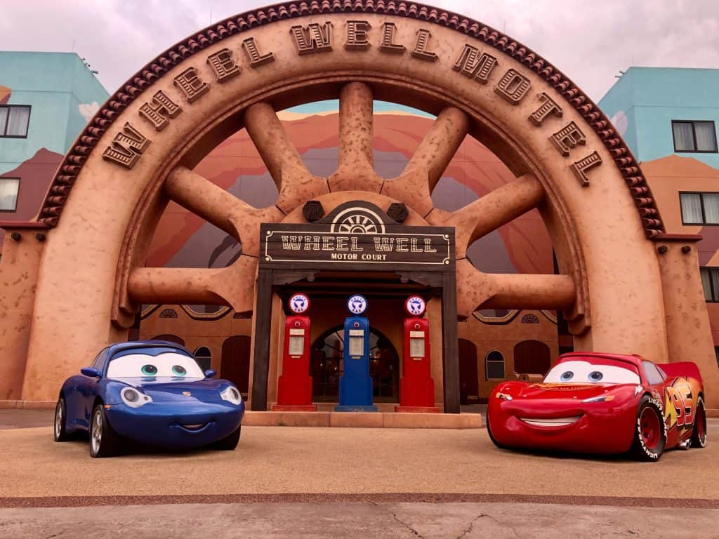 """Art of Animation Cars theming with two cars outside the entrance with a big """"Wheel Well Motel"""" sign and gas pumps around them"""