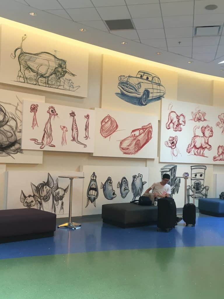 A man sitting on a chair in front of hand-drawn artwork at Disney's Art of Animation resort