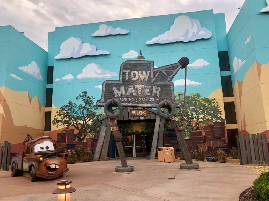 """Entrance to building at Disney's Art of Animation Resort with a Cars character in front and a sign saying """"Tow Mater Towing and Salvage"""""""