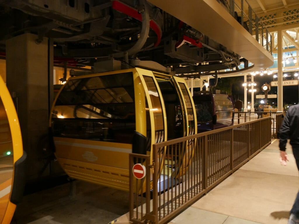 A Disney Skyliner car with open doors inside a station