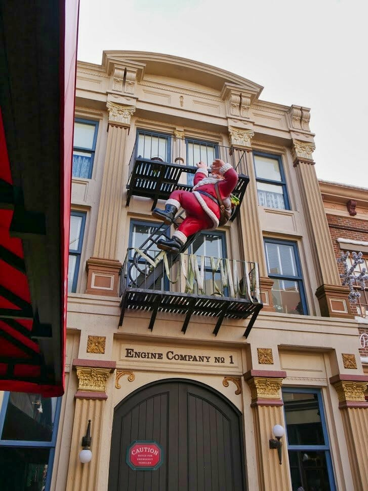 Father Christmas climbing an emergency escape stair case outside a building at Hollywood Studios