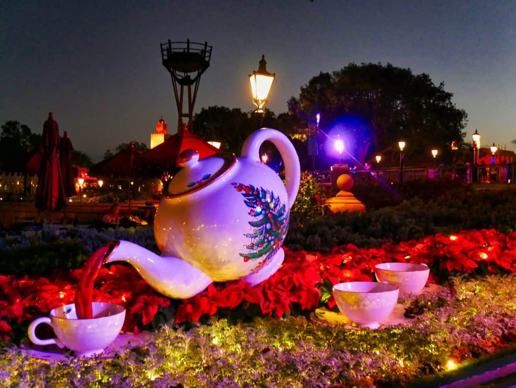 A teapot statue with a Chistmas tree painted on the side at Epcot at Christmas