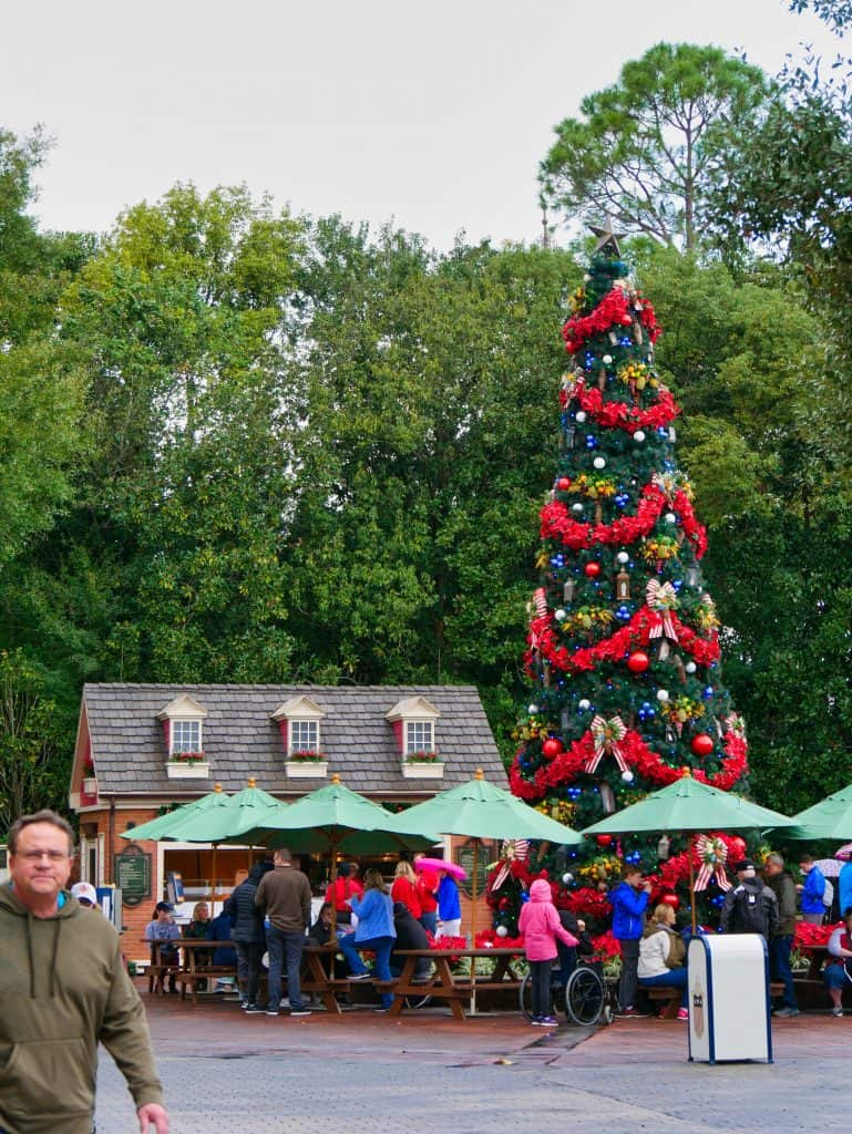 A Christmas tree with people eating underneath it under umbrellas at Epcot, Disney World at Christmas