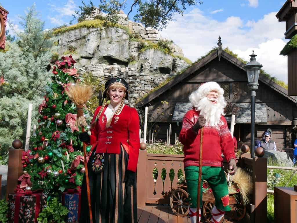 A Father Christmas character and female character on stage in the Norway area at Epcot, Disney World at Christmas