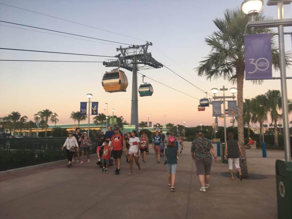 People walking under the Disney Skyliner