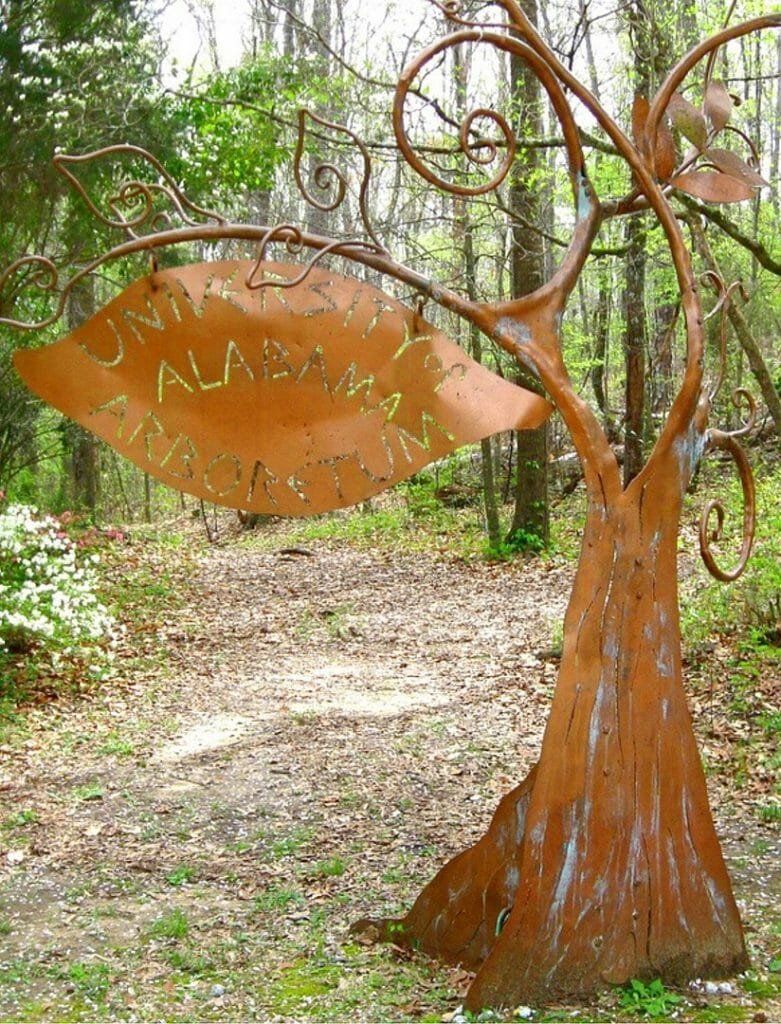 A copper sign made to look like a tree at the University of Alabama Arboretum