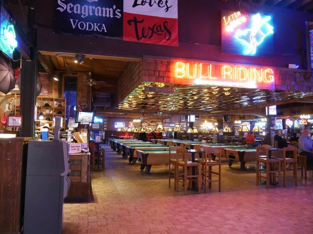 "Inside of Billy Bob's in Fort Worth, with pool tables and a big neon sign that says ""Bull Riding"""