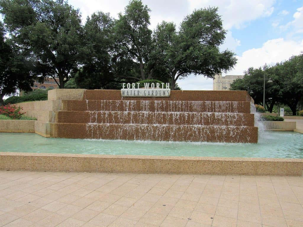 A pool of water and water flowing from a sign for the Fort Worth Water Gardens