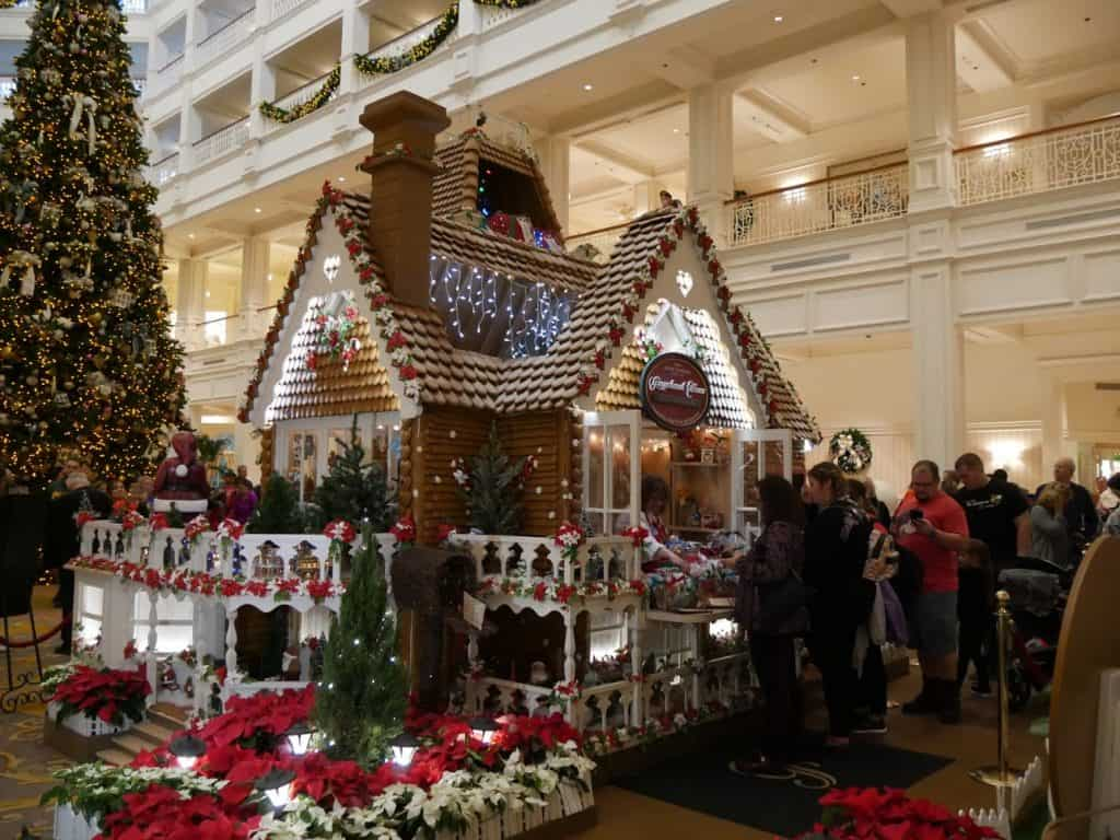 A Disney gingerbread house with people shopping at the Grand Floridian Disney World resort at Christmas