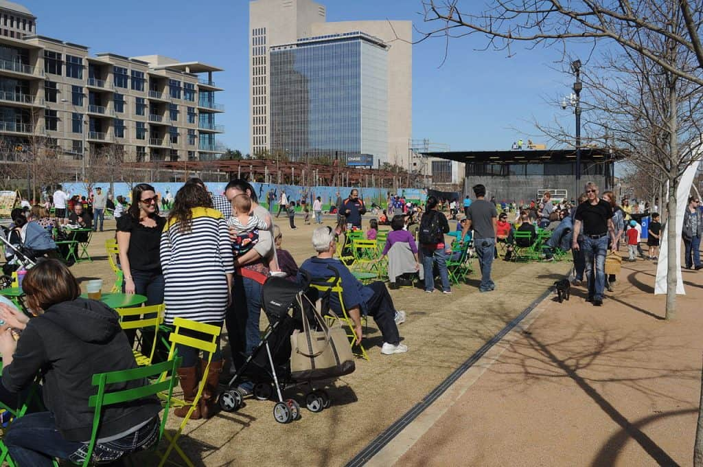 Many people on chairs and standing talking in a park with buildings behind, at Klyde Warren Park in Dallas