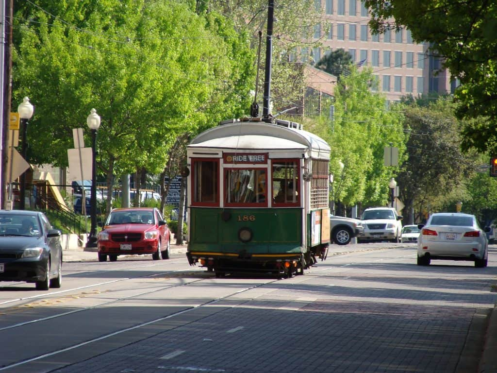 A trolley traveling down a road with cars either side in Texas