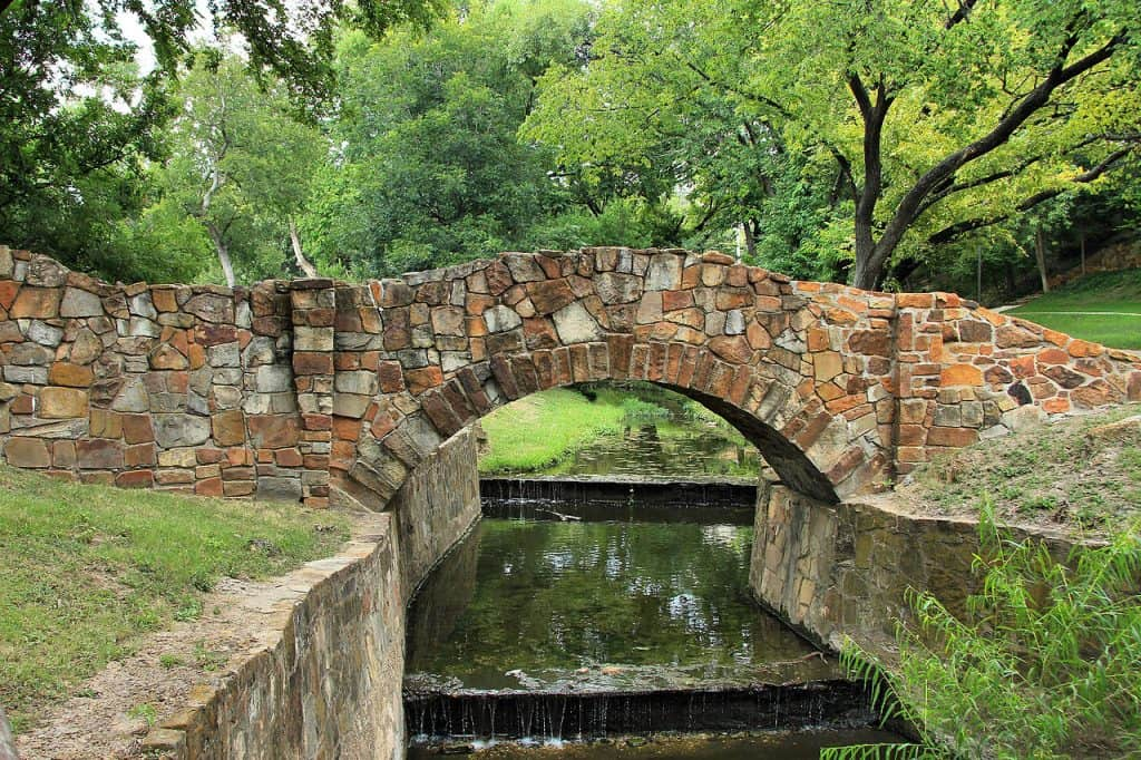 A stone bridge going over a stream in Reverchon Park in Dallas