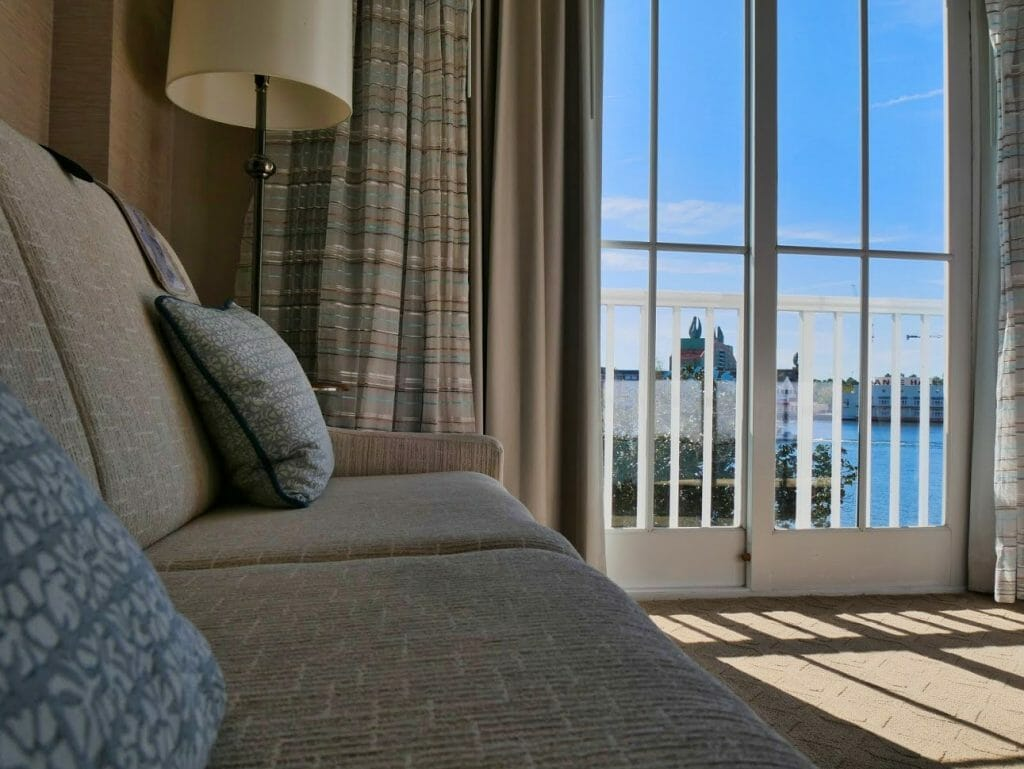 A nice couch with a view out of a balcony over water in an upgraded room at Beach Club resort