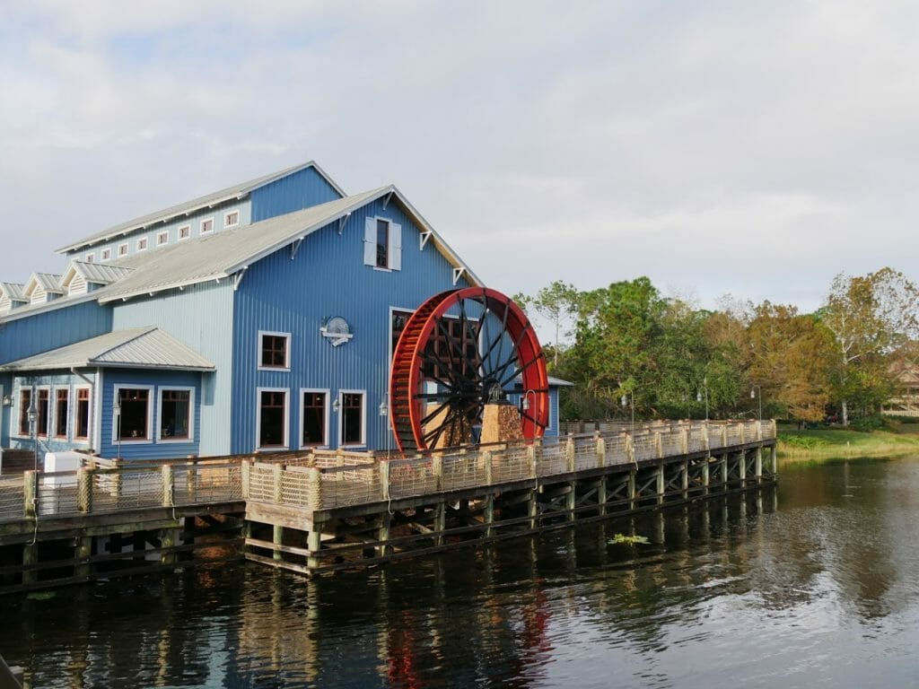 A blue wooden building with a red water wheel