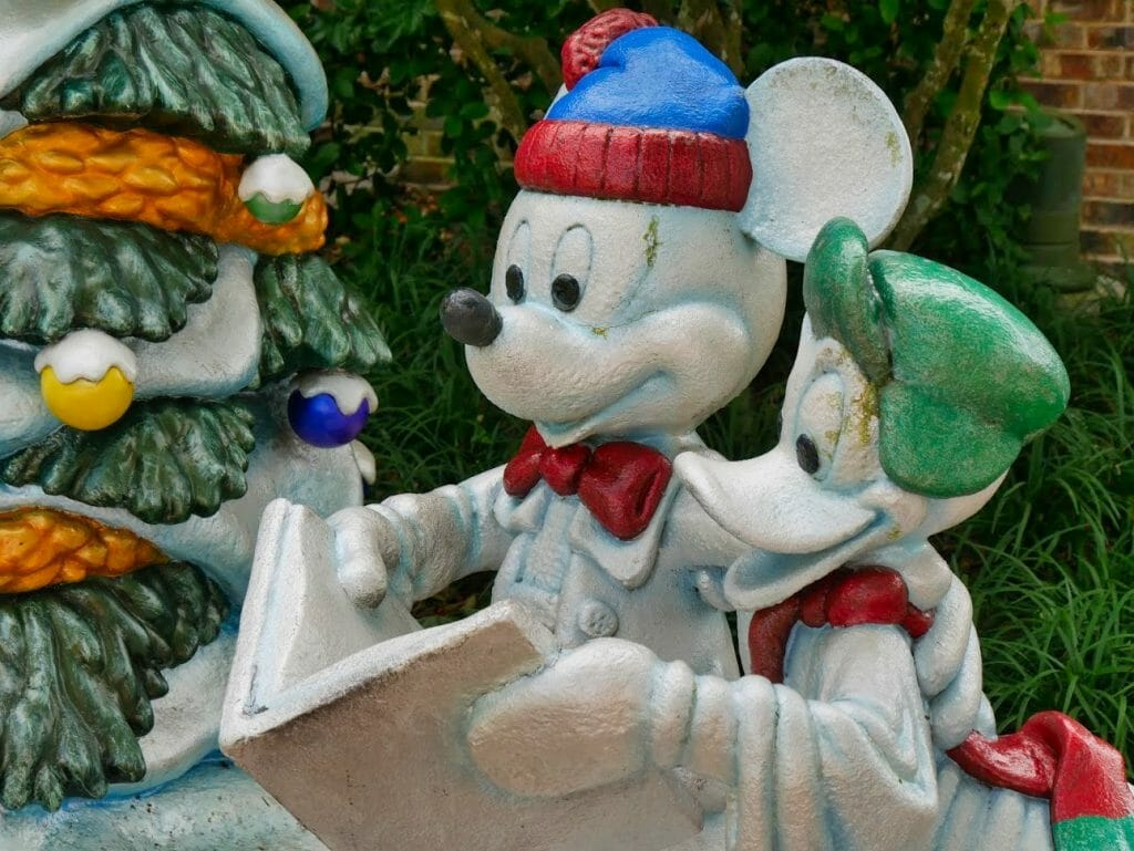 Mickey and Donald as snowmen singing from a Christmas carols book at the Disney Springs Christmas Tree Trail
