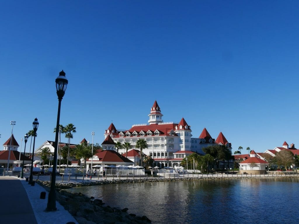 The Grand Floridian Resort Disney World with a lake in front on a blue sky day
