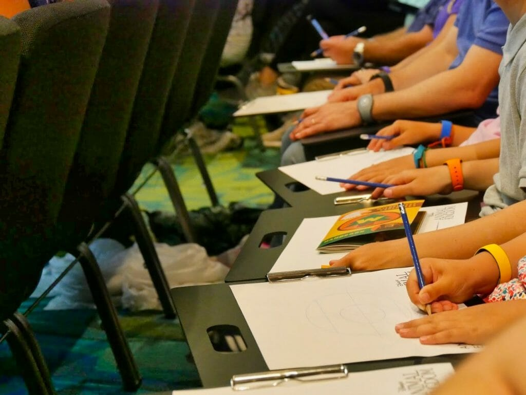 People with paper and pencils at a free animation class at Disney