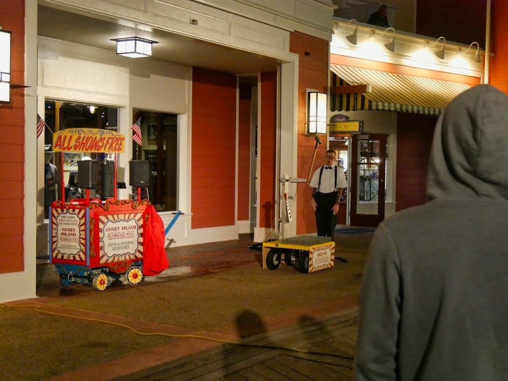 A free comedy show at the Disney Boardwalk with a man with spikes on a table and a large hammer