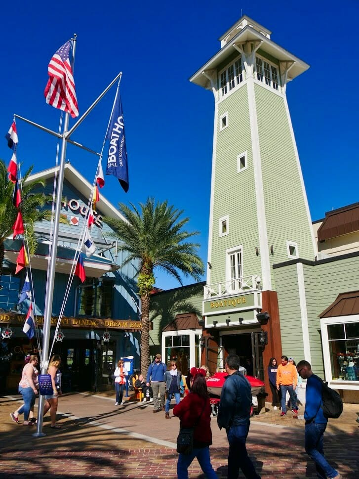 A tall green tower and restaurant building at Disney Springs