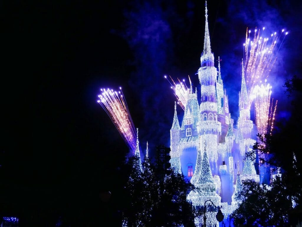 Disney World castle lit up at night with fireworks