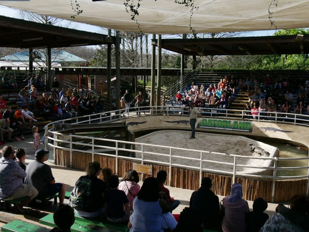 A man doing a show inside an arena with people watching at Gatorland Florida