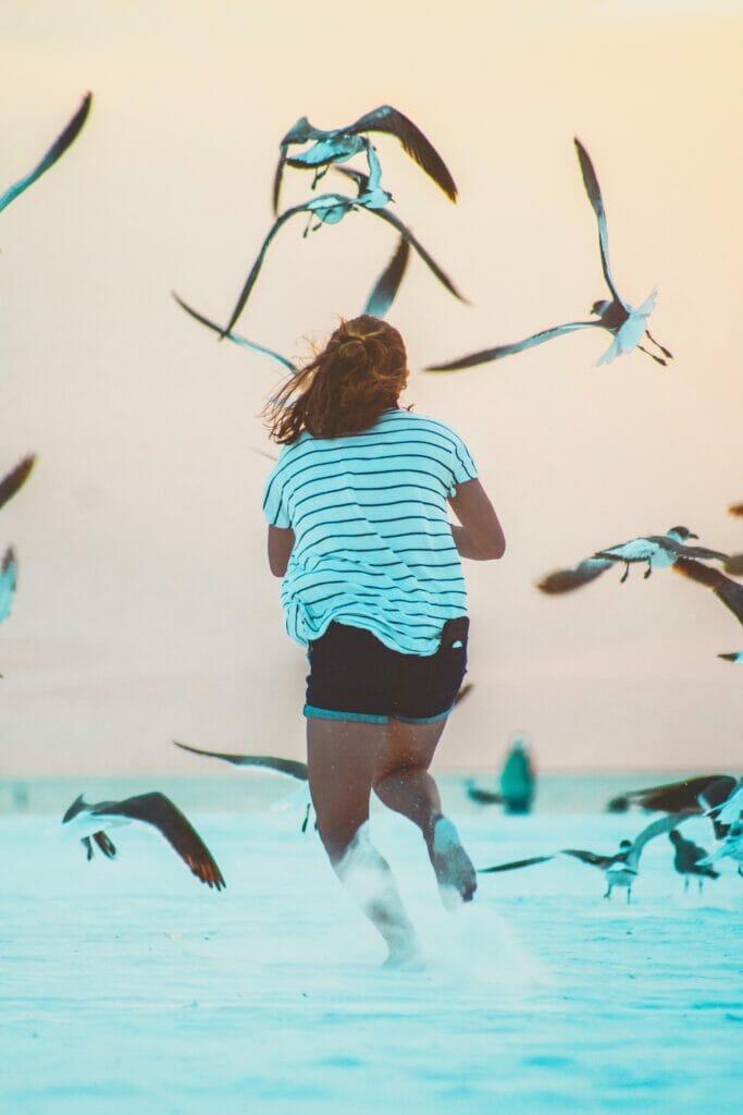 girl running through sand with birds flying
