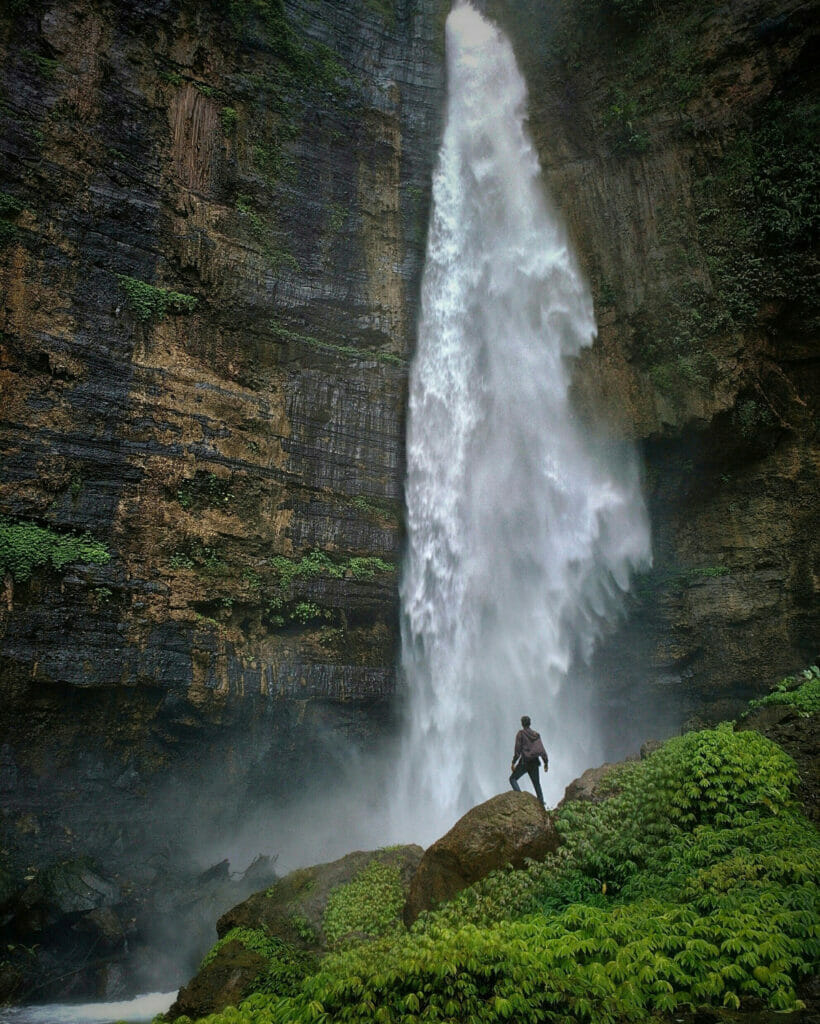 man in front of a waterfall