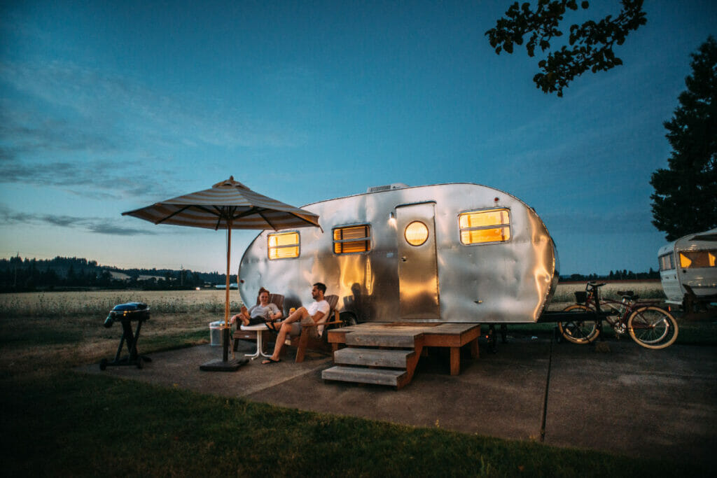 camper rv with two people sitting in front of it