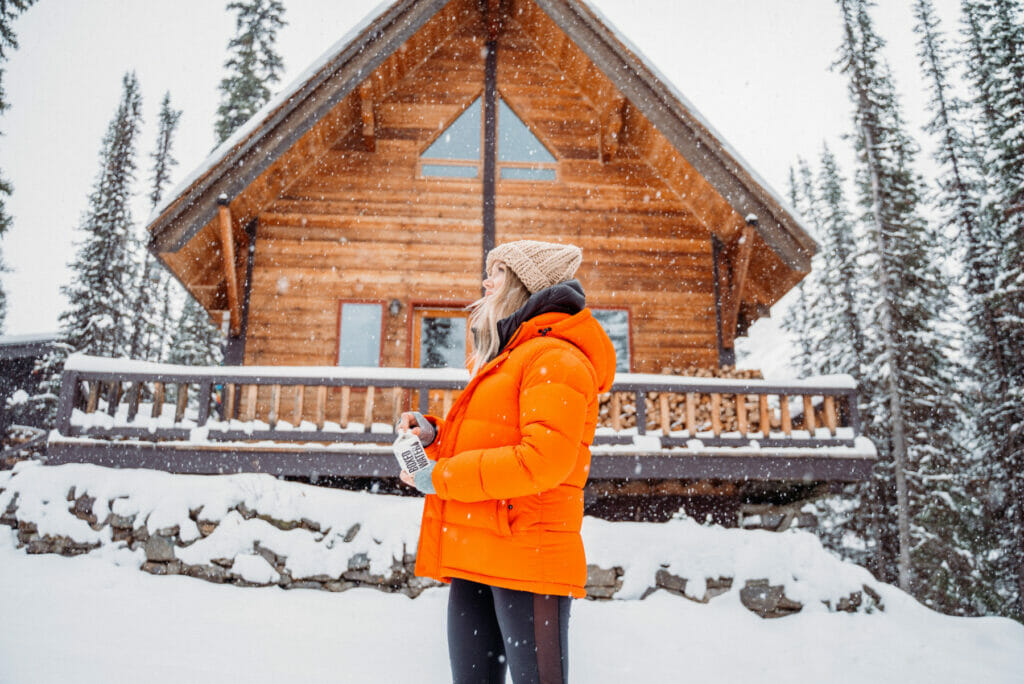 woman in orange jacket standing in front of a cabin in the snow