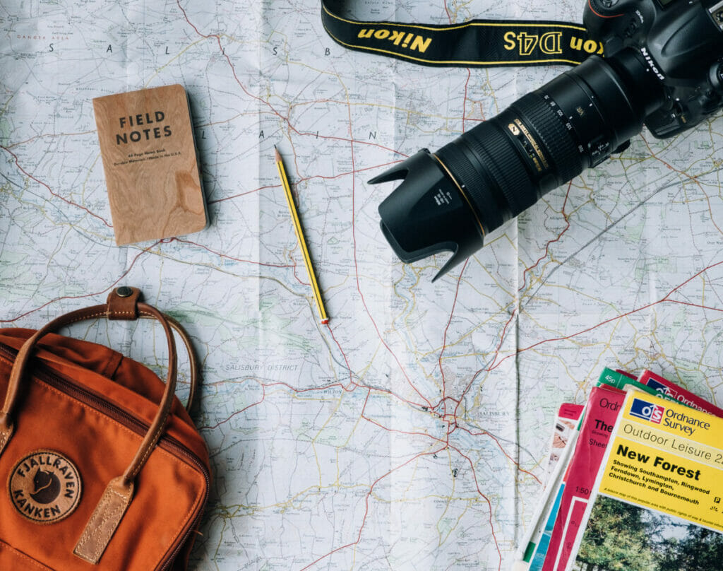 camera, backpack, and field notes on a map.