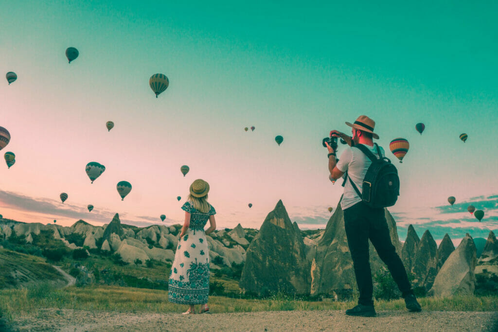 couple taking pictures of hot air balloons.