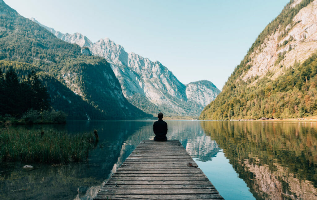 man sitting on the end of a dock looking at mountains.